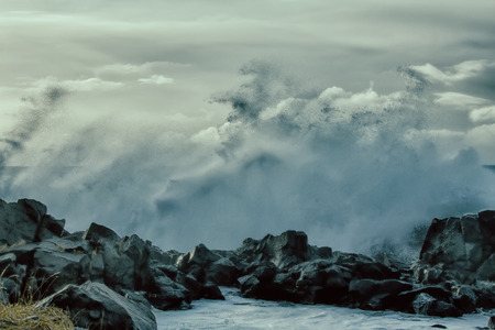 turbulent waves of Pacific ocean and rugged beauty of basalt rocks
