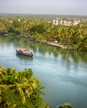India, Kerala - January 10, 2016: backwaters, India. Tropical landscape. Channels with ships (famous Waterhouse) and towns under palm trees