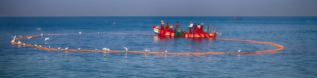 heard: India, Kerala - December 27, 2015: Indian fishermen graphically pull painted Seine right in boat 2. Net painted in bright colors, flying terns, wooden boat. Heard Hindu hymns Editorial