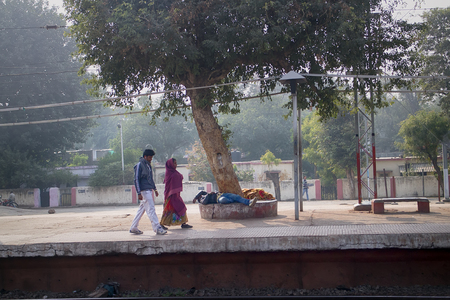 miserable: India, Delhi - Dec 28, 2015: Indian Railways. Platform of station. For an Indian sleeping on street business as usual, more liberated morals