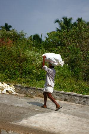 India, Karnataka - January 17, 2016: Proletariat. Baggage handler - toil of Indian coolie worker