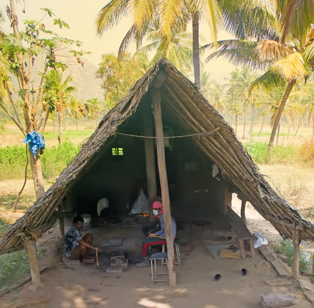 farriery: India, Kanakapura - February 14, 2016: Indian life. Primitive village smithy in palm tree grove and blacksmiths with tools