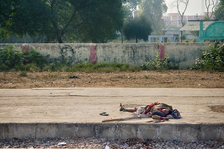 legged: India, Delhi - Dec 28, 2015: Indian Railways. Platform of station. For an Indian sleeping on street business as usual, more liberated morals. Disabled person (dot and go one) sleeps directly on concrete because it is always warm