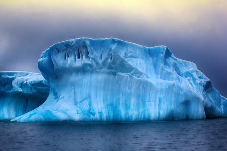 Iceberg fanciful shapes - slick hurricane-force winds and storm waves, blue fresh ice. Franz-Joseph Land, Rudolf island