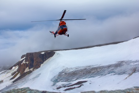 Journey to high Arctic latitudes. Helicopter brings scientists and extreme tourists on harsh polar Islands with glaciers, wild cliffs and snowfields Franz-Josef Land - two steps to North pole Stock Photo