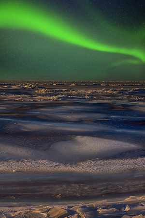 Northern lights over ice sea. winter and night in cold green lights phenomenon