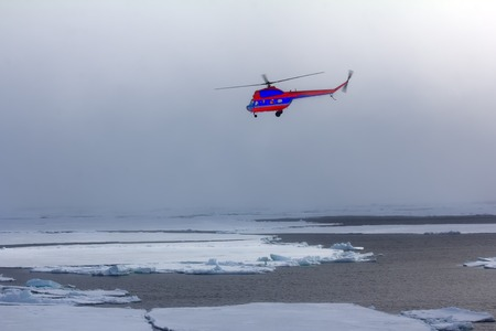 Near the North pole. Ships helicopter in fog at Arctic ocean (pack ice), air transport in bad weather conditions (utility aviation, leisure aviation)