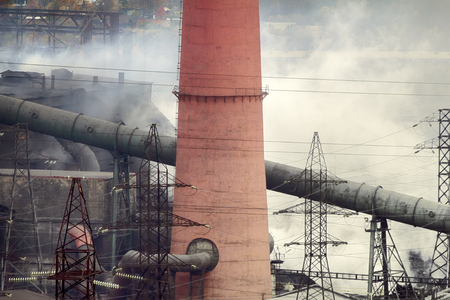 visible: Heavy industry, harmful production. Old forties Copper-Nickel plant in smoke (smoulder roof). Visible thick antediluvian pipeline. Air pollution