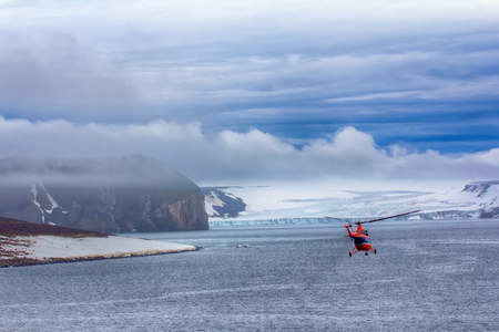 Journey to high Arctic latitudes. Helicopter brings scientists and extreme tourists on harsh polar Islands with glaciers, wild cliffs and snowfields/ Franz-Josef Land - two steps to North pole Stock Photo - 81284972