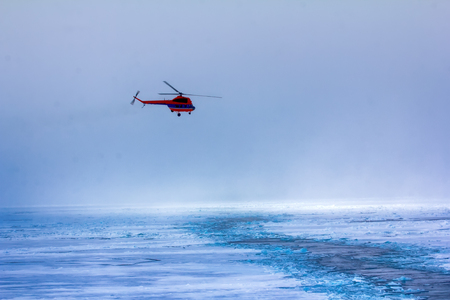 Near North pole. Ships helicopter in fog at Arctic ocean (pack ice), air transport in bad weather conditions (utility aviation). Over icebreaker channel. Reconnaissance of ice conditionssituation