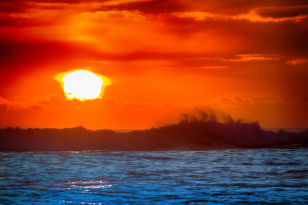 filled with colors of marine tropical sunset. wave splash is rolled on beach Stock Photo
