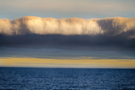 Front of cloud system (weather barrier). Dense vertical clouds near the storm core (eye wall of the cyclone) above sea Stock Photo