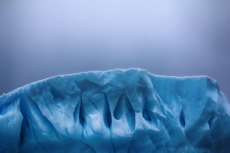Iceberg fanciful shapes - slick hurricane-force winds and storm waves, blue fresh ice. Franz-Joseph Land, Rudolf island