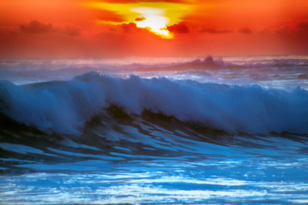 navy blue background: filled with colors of marine tropical sunset. wave splash is rolled on beach Stock Photo