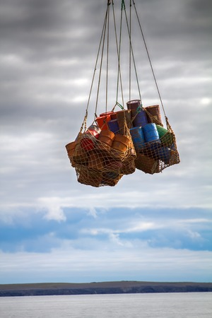 Air cargo and aviation work, cargo air service, lift helicopter. Helicopter carries sling (rope mesh) with empty metal barrels