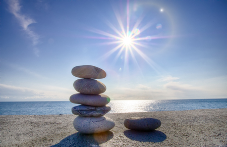 Entertainment for beachgoers. Cairn, cone is formed of pebbles on seashore, with waves always