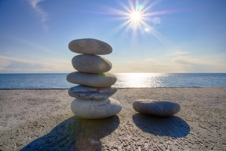 briny: Entertainment for beachgoers. Cairn, cone is formed of pebbles on seashore, with waves always