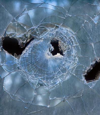 background broken window during riots. glass pieces hole mayhem
