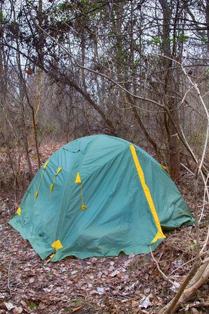 tent in foothills in dense thickets hidden. wild tourism is not a populated area