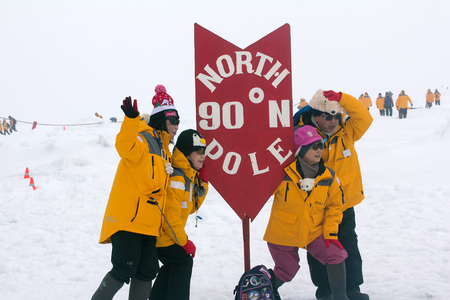 North pole - 15 July 2016: Best Arctic journey. Entertainment tourists. Pointer of geographical North pole poit where all longitude and 90 degrees latitude. Chinese tourist takes picture