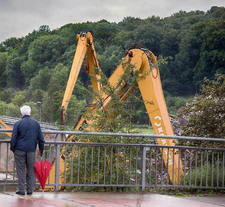 Near Stuttgart , Germany - September 12, 2017: Passer-by with red umbrella, casual observer is process of sorting waste and loading