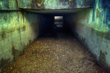 Military tourism and video Wargame. Underground military bunker from second world war in Baltic: doors, concrete and rebar, steel ceilings. Tunnel and light at end - hope for victim