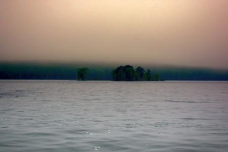 Huge lake Onega in Western Russia. Forest cape in haze