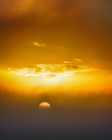 The setting sun in the misty haze. Yellow summer sunset promises Sunny weather the next day