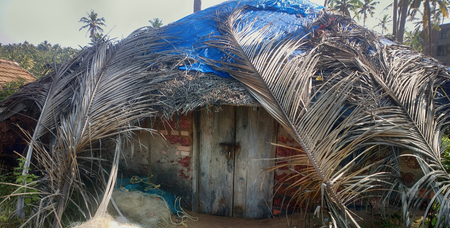 Fishing half dugout (pandal) covered with palm leaves on shores of Arabian sea, fishing nets are on verge of. Kerala