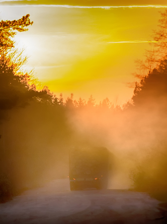 Blurred background. forestry management truck loaded with wood logs in mist at sunset on a forest road