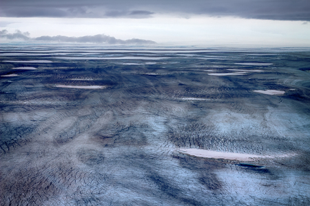 boundary of accumulation zone of dome cover glacier in peak summer. Weakly fractured undulating glacial plain. Novaya Zemlya Archipelago. North Island. Photo from helicopter 2012