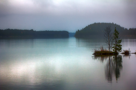 Brooding landscape with islets. Quiet sad fall day on serene lake, fog light Stock Photo