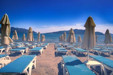 Les plages méditerranéennes attendent les touristes. Transats, chaises longues, parasols, tables à manger et palmiers sur la plage - Ou le contraire: la saison des plages est terminée, station balnéaire