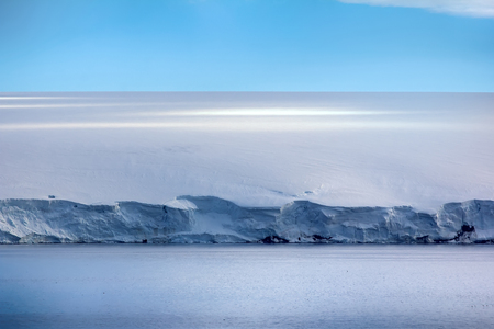 Islands along British channel. Glaciers, icefall, outlet glacier, snowfields and rock outcrops. Glacial shield of George Land and Hayes Island. Above line of cliffs is the ice dome. Franz Joseph Land