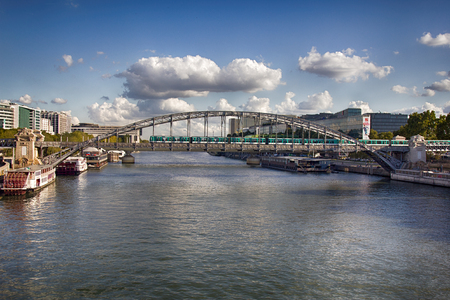 Paris, France - September 22, 2017: Seine river with arched bridge to subway trains and moored pleasure boats, pleasant autumn day with cumulus clouds, banks of Seine, quay javel andré citroën Editorial