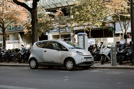Paris, France - September 23, 2017: owner recharges batteries of your electric car at charging station, motor scooter Parking