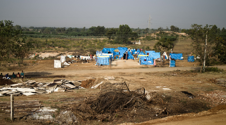 Tent city of poor people around railway. Settlement of refugees, refugee camps, jungles
