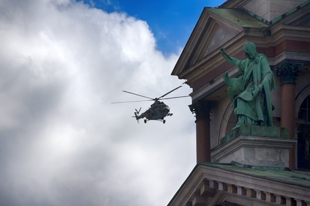 Saint Petersburg, Russia - May 9, 2017: Mi-8amtsh Terminator, NATO code Hip. Russuan Transport-attack helicopters flies over city over temple with bas-reliefs and figures of saints Editorial