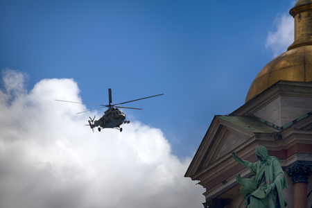 Saint Petersburg, Russia - May 9, 2017: Mi-8amtsh Terminator, NATO code Hip. Russuan Transport-attack helicopters flies over city over temple with bas-reliefs and figures of saints, Golden church dome