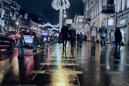 Festive, public holiday in Northern city Saint Petersburg. Cold brightening of building illumination and decorative string in harmony with climate. Nevsky prospect