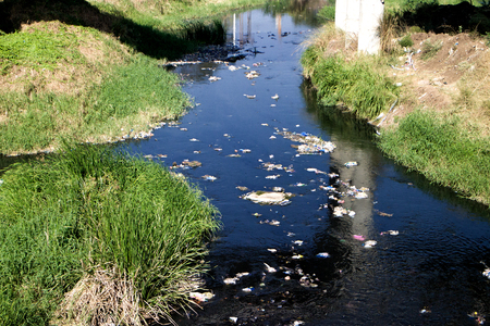 Contaminated stream, flotsam. Plastic and other debris floating on river from city Stockfoto