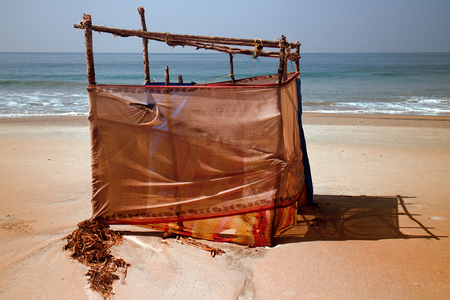 Primitive cabana (changing stall) on tropical beach in winter after storm. Beach-related rest, beach holiday, gentle sun-tan Stock Photo