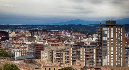 Romantic white city on hills - Spanish town Girona in foothills of Pyrenees - between peaks of Pyrenees mountains and Mediterranean sea. New city