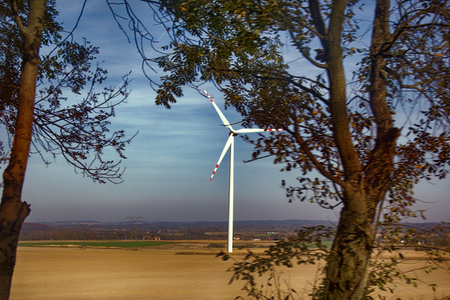 Wind turbines among open space of Europe. Alternative energy sources in European Union. Wind machines in fields against bright sky, sunset. Energy programme of EU, Energy Commission, renewable energy