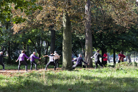 Paris, France - September 23, 2017: Middle-aged and elderly people are engaged in physical exercises in Park to maintain tone in open air. Healthy lifestyle. Rapid aging of Europes population