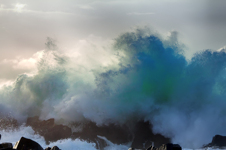 Wall of water like tsunami - turbulent waves of Pacific ocean more than 8 meters (heavy) and rugged beauty of basalt rocks (reef, cay cavity, shoal head) Stock Photo