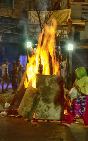 India, new Delhi - March 1, 2018: crazy streets of Delhi during Holi celebration. huge bonfires right in the streets. people go close to the fire and heat