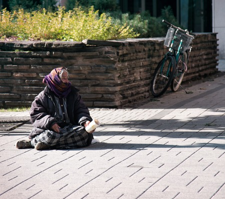 HELSINKI, FINLAND - AUGUST 24, 2017: The old woman begging on the street
