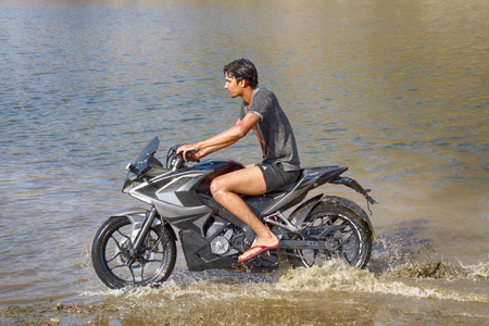 India, Udaipur - March 25, 2018: young motorcyclist rushes in the water in a spray at high speed 新聞圖片