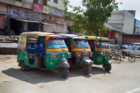 mechanical and Bicycle taxi rickshaws waiting for customers. Indian city transport. Editorial